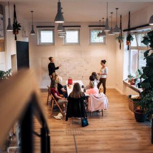 Zdjęcie przedstawia wnętrze Domu sąsiedzkiego i stolik, przy którym siedzą osoby podczas warsztatu.